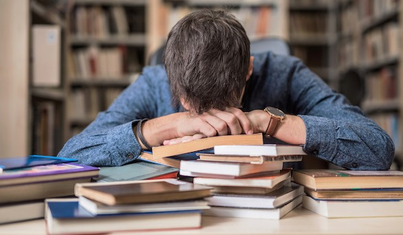 student with head on books