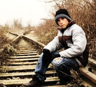 boy on railroad tracks