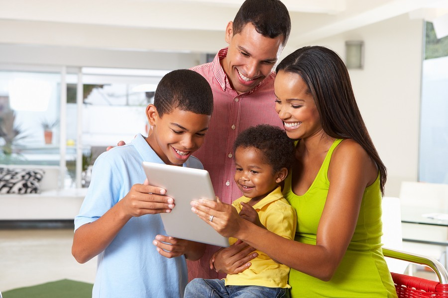 mom, dad, and kids with tablet