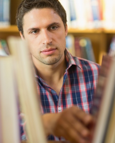 image of man doing research in library stacks