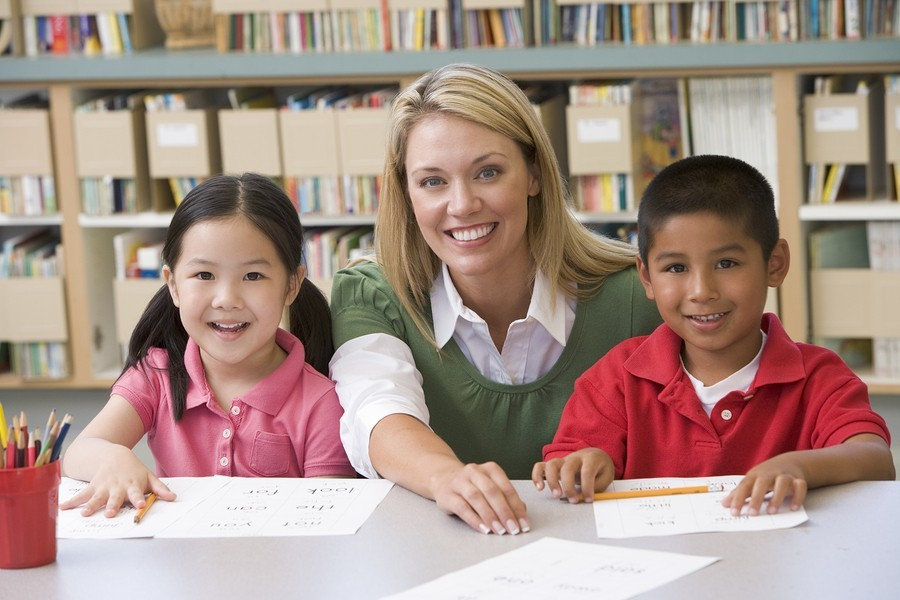 image of boy and girl with teacher in school library