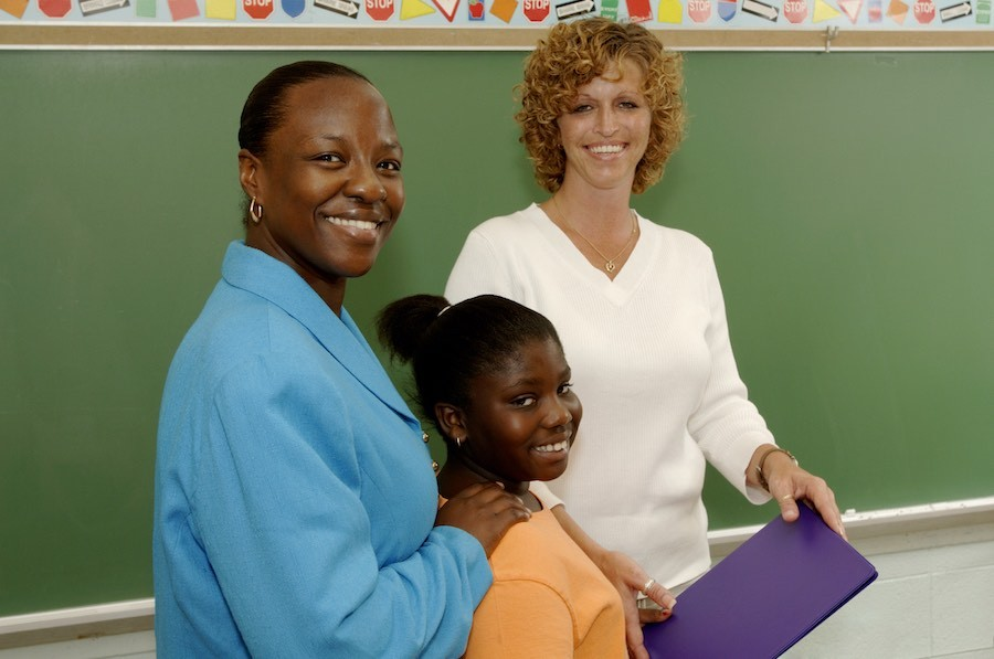 mother, daughter and teacher in front of school blackboard