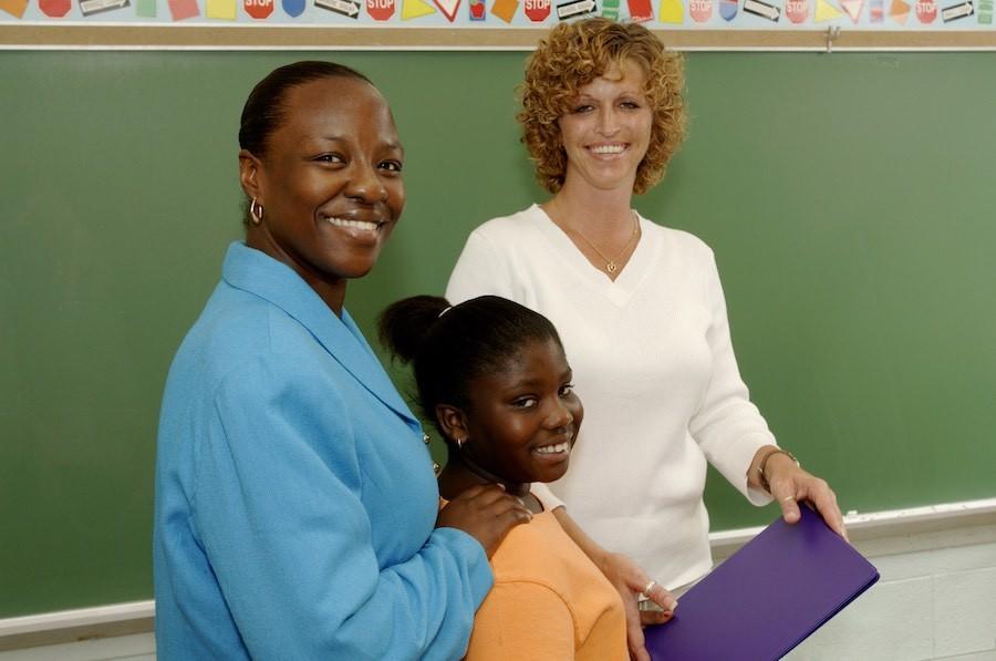image of girl, parent, teacher in classroom