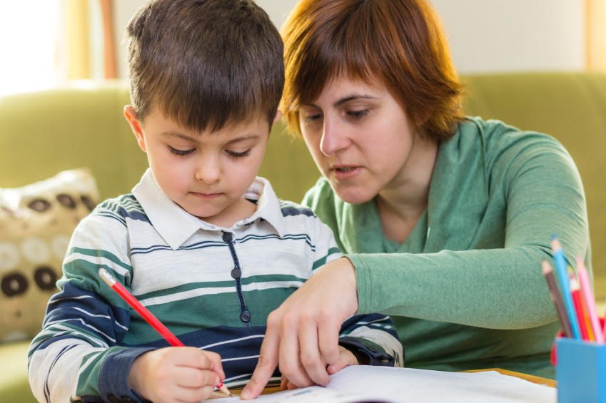 boy struggling with homework with mom