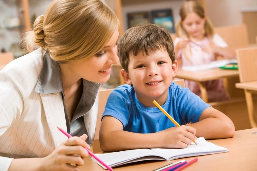 image of boy writing with tutor or evaluator