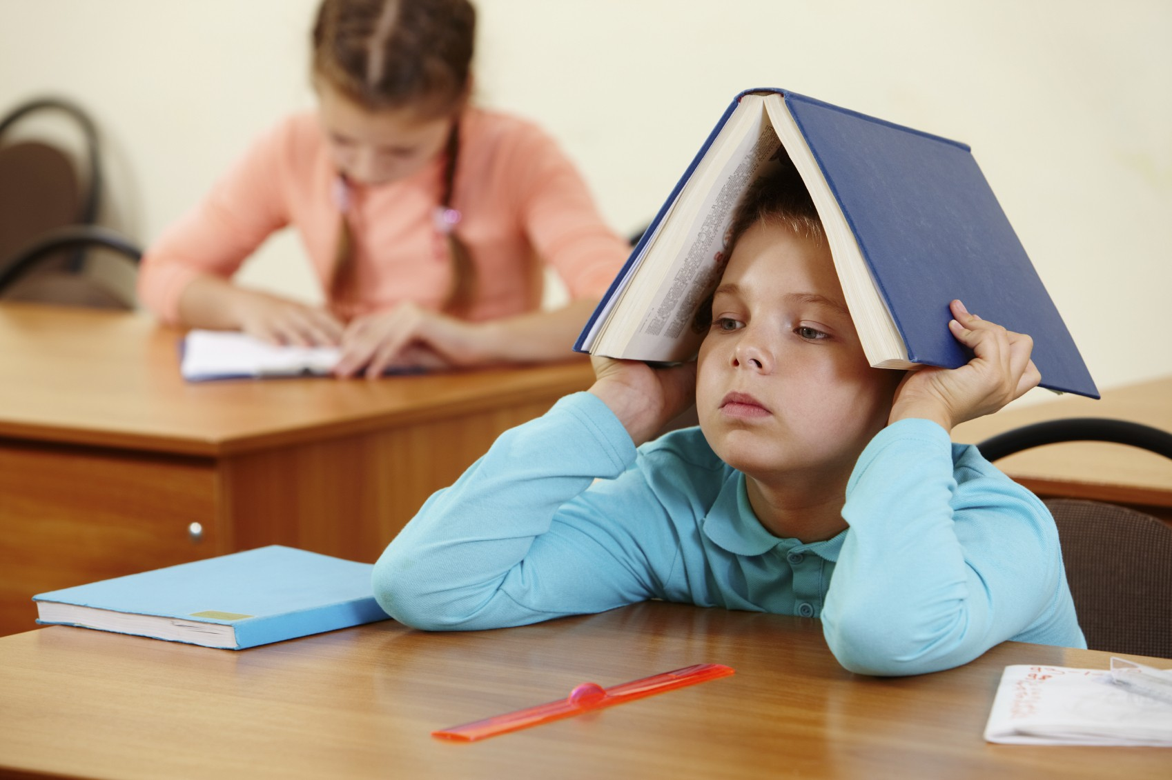boy in class with book on head