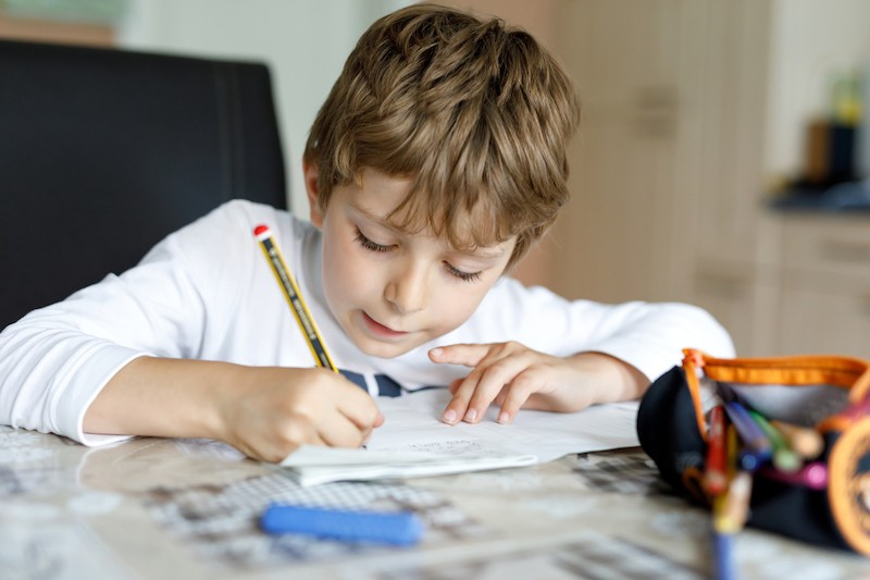 image of boy writing in class