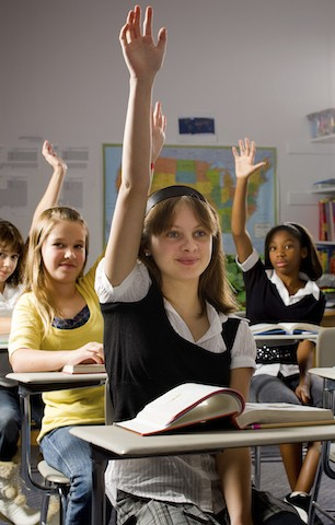 girl in class with hand raised