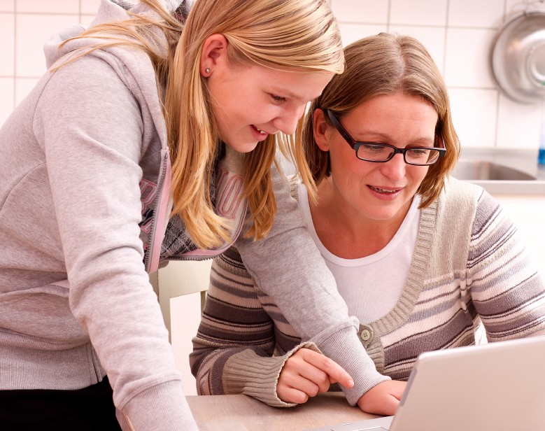 girl teen and mom at computer together