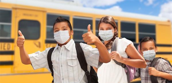 3 children standing in front of school bus