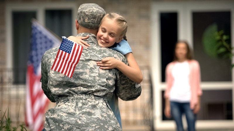 image of soldier dad with daughter and flag