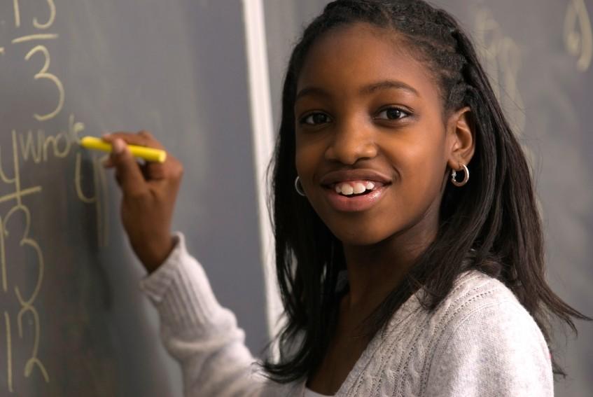 girl student doing math at blackboard