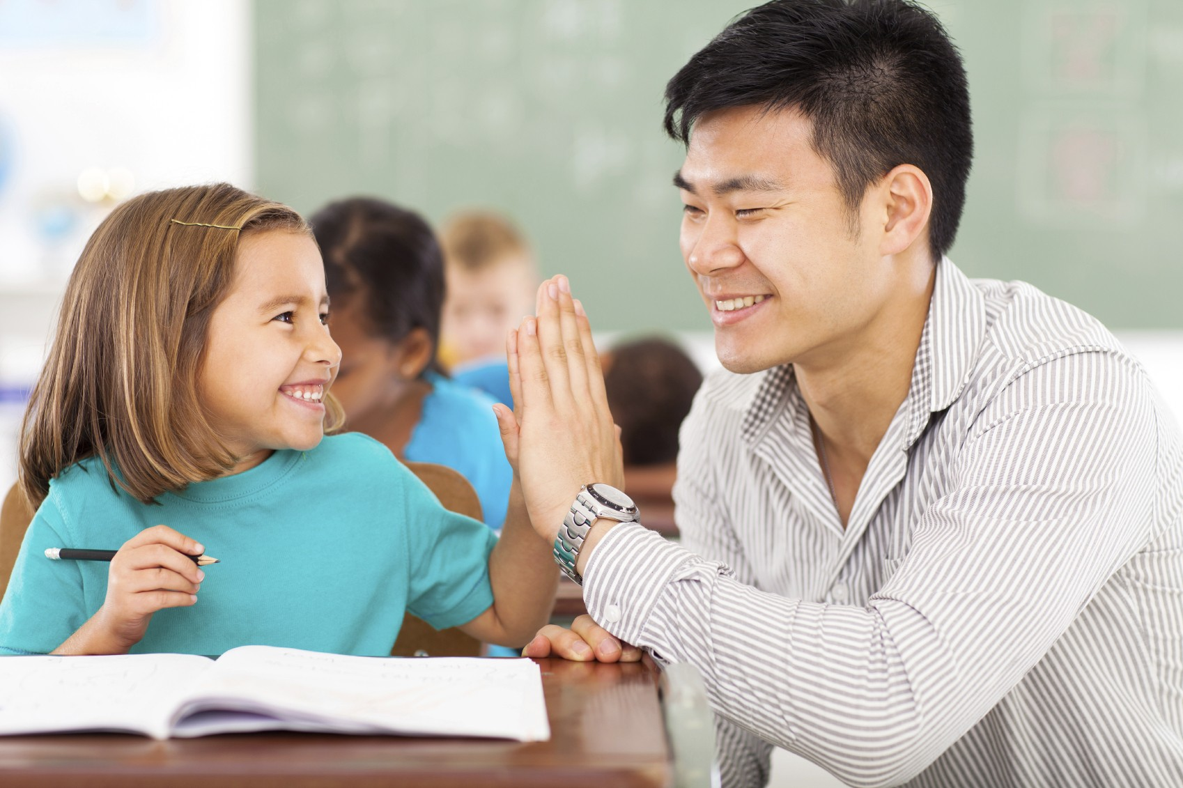 teacher and student high five in class