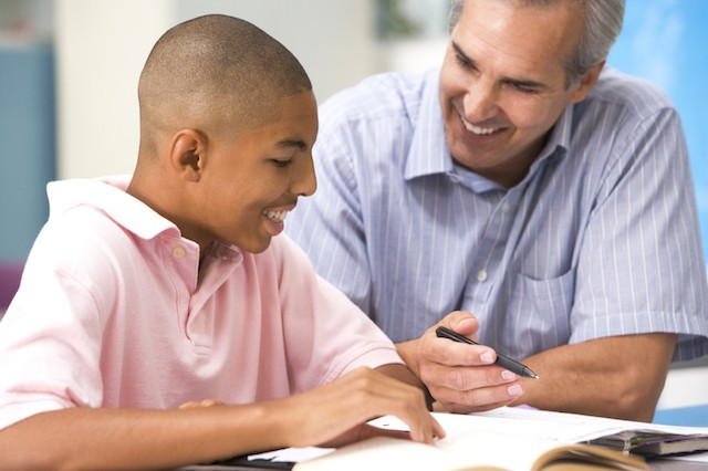 image of teen boy reading with tutor or teacher