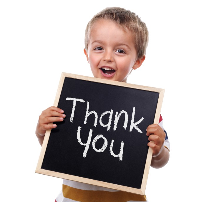 Young boy with a thank you sign