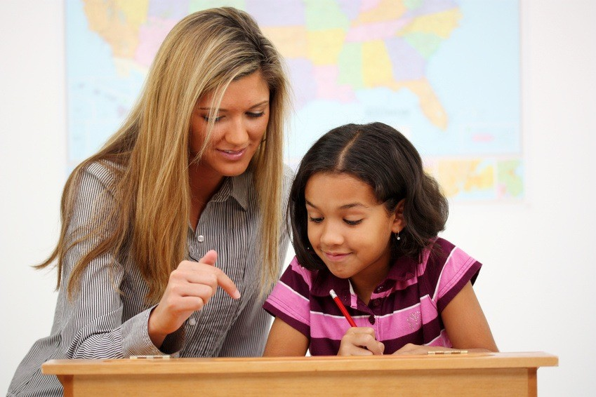 teacher and student girl reading in school