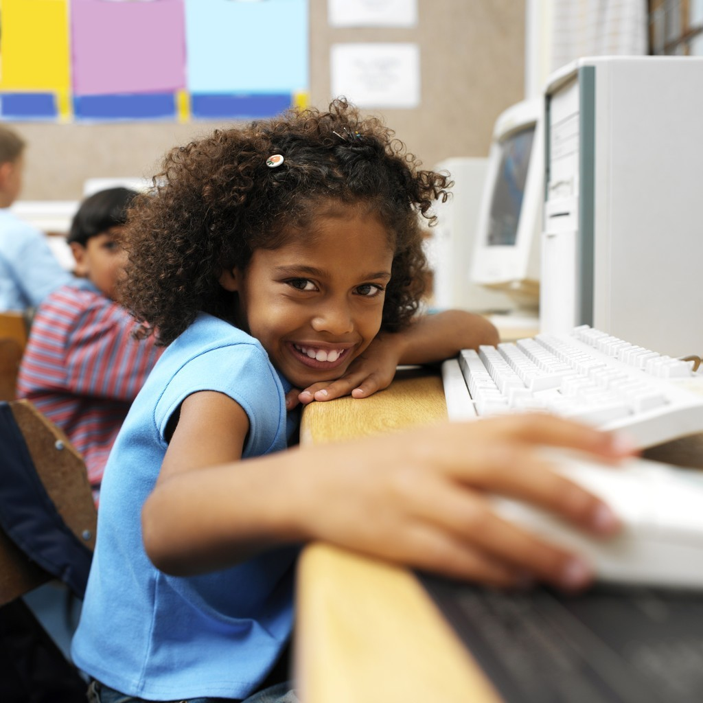 young girl at the computer smiling
